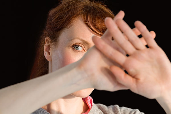 Scared woman covering her face on black background